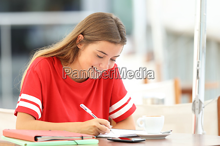 happy student girl taking notes in
