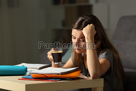tired student studying late hours drinking