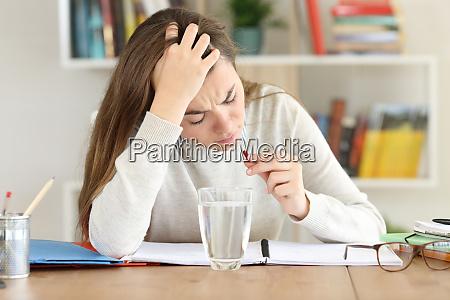 uncomfortable student taking painkiller pill at