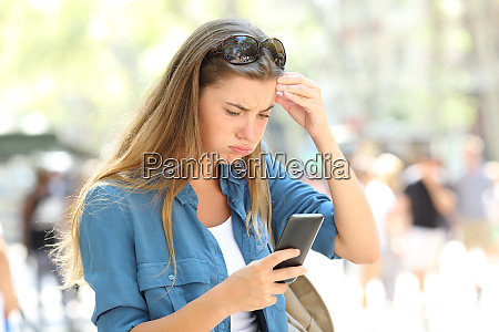 frustrated woman reading phone content in