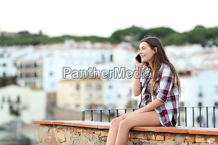 happy teen talking on phone sitting
