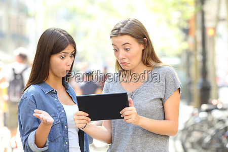 confused friends reading online content in