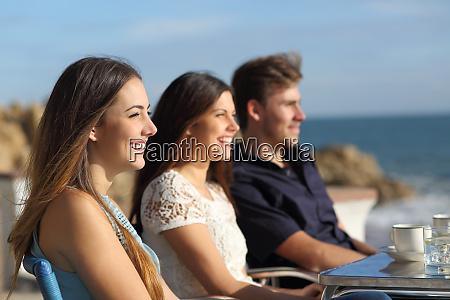 three happy friends watching the beach