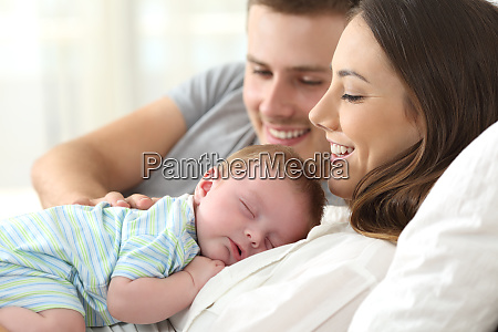 parents watching their baby sleeping