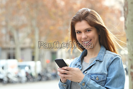 happy teen holding a cell phone