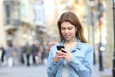 happy teen texting messages on phone
