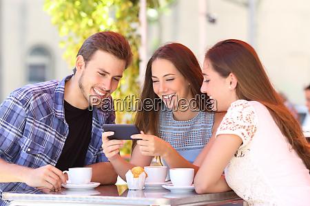 three friends watching smart phone media
