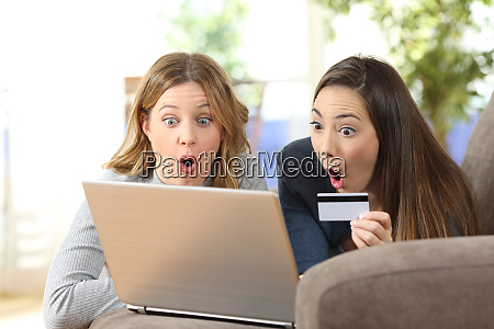 amazed friends buying online together at