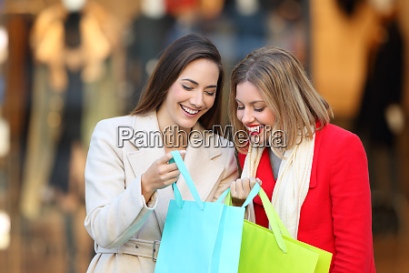 two shoppers showing products in shopping