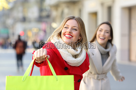 two happy shoppers running on the