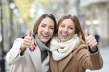 two friends smiling at camera with