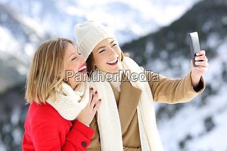 friends taking selfies in a snowy