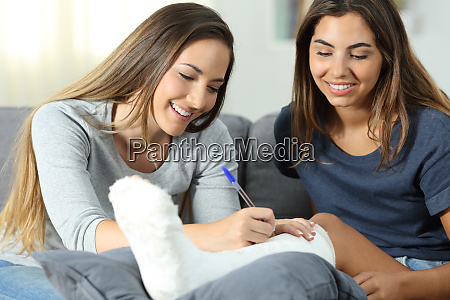 friend signing in a plaster foot