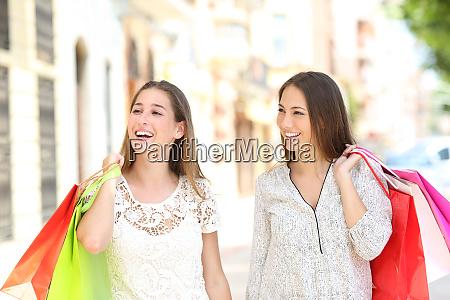 two shoppers walking in the street
