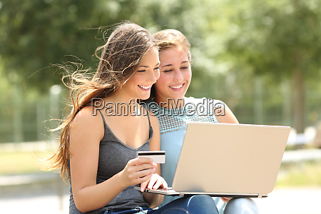 friends paying online with laptop and