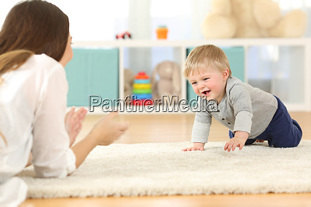 baby crawling towards his mother
