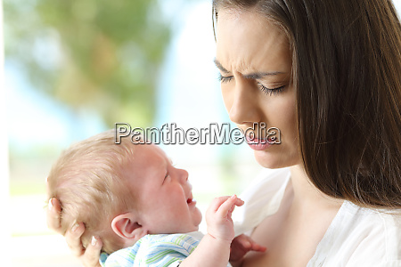 tired desperate mother and baby crying