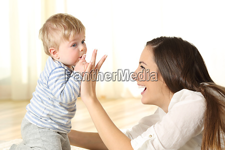 baby kissing his mother finger