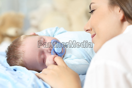 mother watching her baby sleeping on