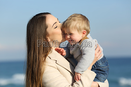 mother kissing her kid son outdoors