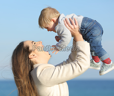 mother raising her baby son outdoors