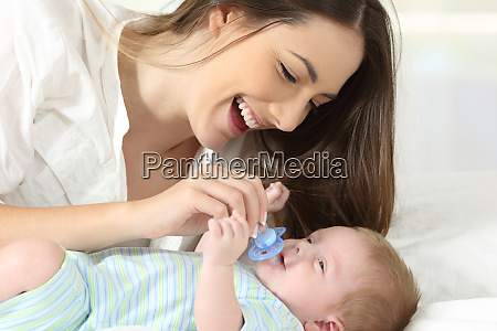 mother giving a pacifier to her
