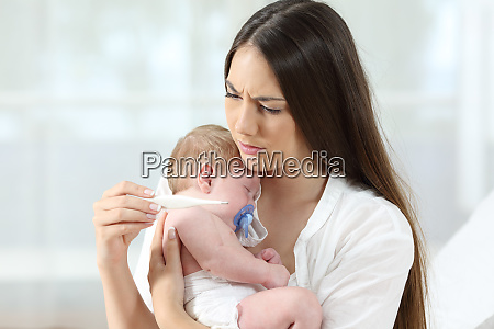 mother checking thermometer with an ill