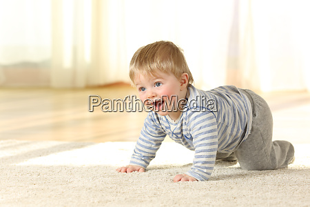 happy baby crawling and laughing on