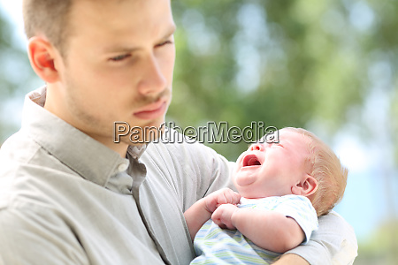 baby crying and bored father