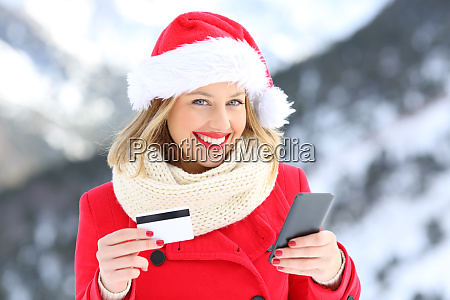 girl on christmas holding credit card