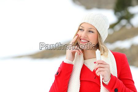 girl protecting skin applying moisturizer cream