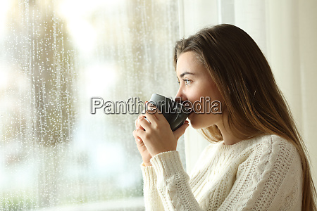 teen drinking coffee looking through a