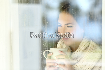 girl looking through a window holding