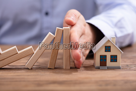 human hand protecting piggybank from falling