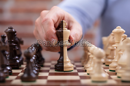 persons hand moving a king chess