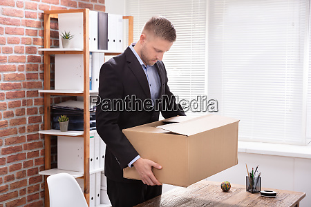 businessman carrying his belongings in office