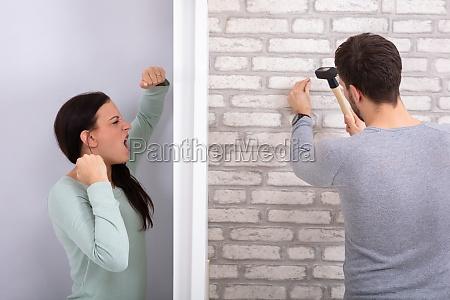 neighbor hitting nail on brick wall