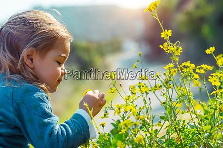 baby enjoying flowers aroma