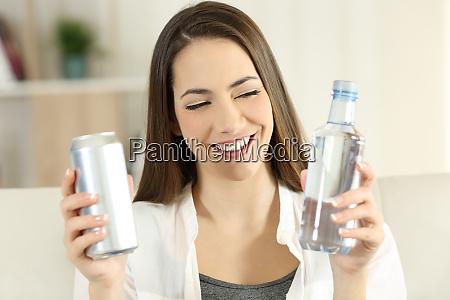 woman deciding between water or soda