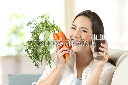 woman showing healthy carrots and water