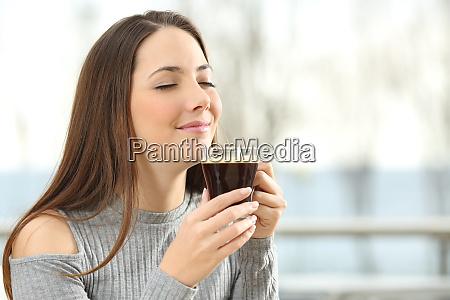 woman smelling coffee aroma