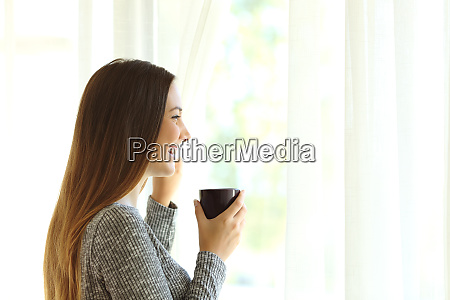 woman relaxing looking through window at