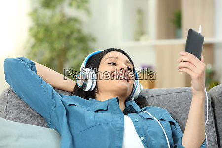 happy woman on a couch listening