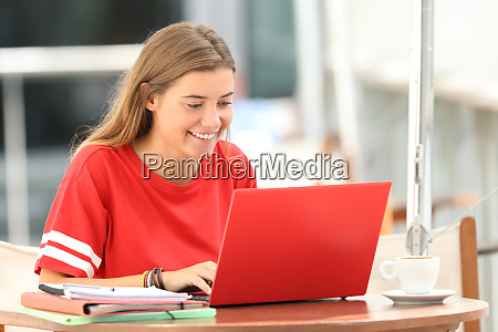 happy student typing in a laptop