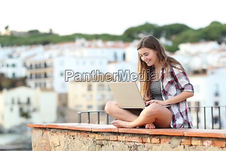 happy teen using a laptop sitting