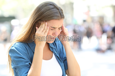 girl suffering migraine in the street