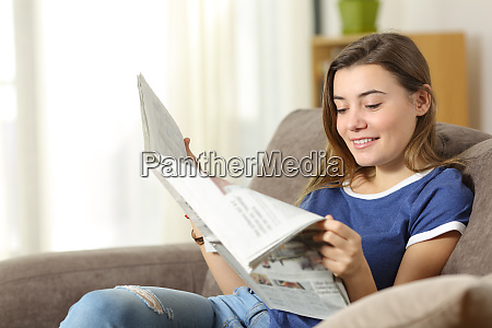 teen reading a newspaper on a
