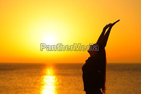 happy woman profile raising arms at