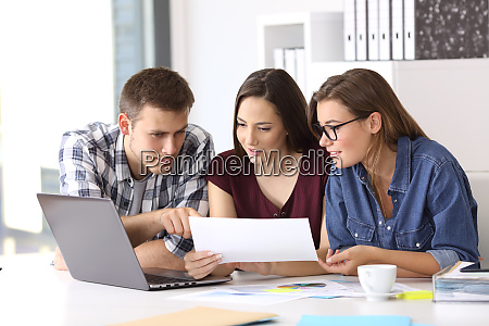 coworkers working at office comparing data