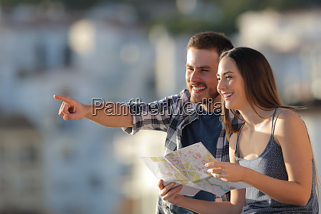 couple of tourists holding map pointing
